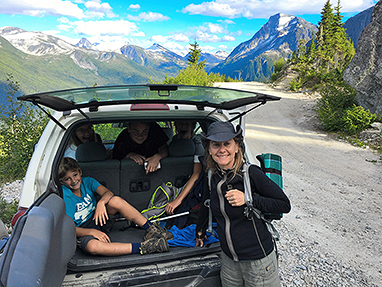 A family up on a scenic tour with their SUV mountains behind.
